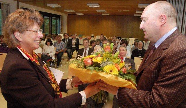 Die kaufmännische Direktorin Barbara Werder heißt den neuen Chefarzt Andreas A. Bünz vor zahlreichen Mitarbeiterinnen und Mitarbeitern der Katholischen Kliniken Lahn mit einem Blumenstrauß willkommen. Foto: SMMP/Bock