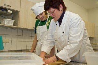 Das Lernen schmackhaft machen: Werkstattlehrerin Ruth Metten mit einer Schülerin in der Küche. Foto. SMMP/Bock