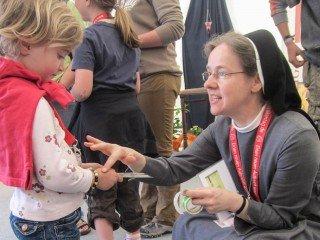 """""""Auch Du gehörst dazu"""" – Sr. Maria Elisabeth Goldmann spricht am Stand der Deutschen Ordensobernkonferenz (DOK) mit einem Kind über die Kirche. Foto: SMMP/Meilwes"""