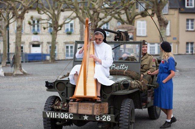 Friedensengel: Schwester Theresita Maria Müller mischt sich während der einwöchigen Gedenkfeier der Landung der Alliierten in der Normandie unter die als Soldaten kostümierten Liebhaber von Militaria und spielt Harfe. (Foto: Andreas Beer)