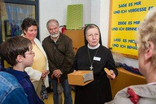 """Schwester Theresia Raabe erklärt diesen Besuchern das pädagogische Prinzip des Bergkindergartens: """"Zeige es mir, und ich erinnere mich. Lass es mich tun, und ich behalte es."""" Foto: SMMP/Bock"""