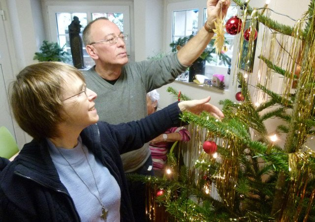 Schwester Klara Maria Breuer arbeitet im Team des Treffpunkts für obdachlose und einsame Menschen an der Clemenskirche in Münster mit. Hier schmückt sie mit Arne den Weihnachtsbaum für die Feiertage. Foto: Hallo Münster