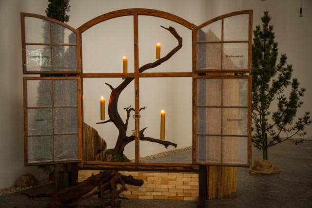 """Der """"Adventskranzkalender"""" in der Dreifaltigkeitskirche des Bergklosters in Bestwig: Eine Idee, die Ikebana-Meisterin Schwester Walburga Maria Thomes nach Jahrzehnten wieder hervorgeholt hat. Jetzt ist das vierte Törchen geöffnet – und die vierte Kerze brennt. Foto: SMMP/Bock"""