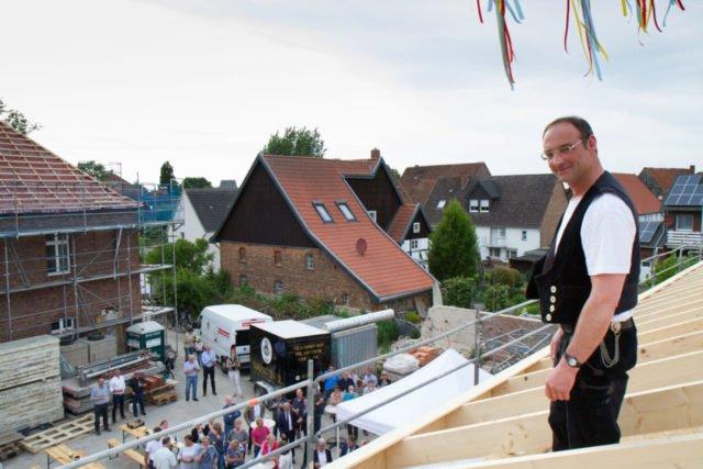 Nach traditionellem Brauch wirft Zimmermann Toni Cramer das Schnaps-Pinnchen vom Dach und wünscht dem Haus und seinen künftigenn Bewohnern alles Gute. Foto: SMMP/Bock