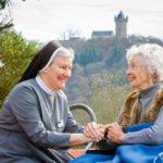 Sr. Theresia Maria Kösters lächelt im Gespräch mit einer 89-jährigen Patientin des Marienkrankenhauses. Foto: SMMP/Bock
